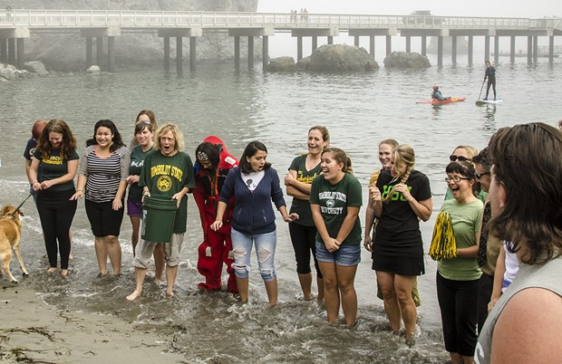 "HSU President Lisa Rossbacher (center-left with bucket) and other participants in the ""Sustainable"" Ice-Bucket Challenge react to water-temperature as a wave washes over their feet prior to their plunge. - MARK LARSON PHOTOGRAPHY"