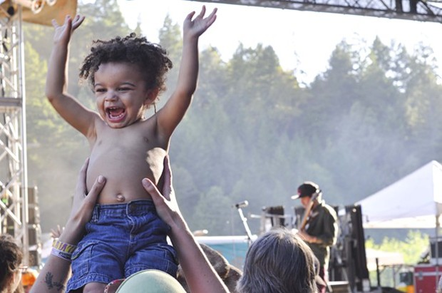 "Indubious bassist/lyricist Spencer ""Skip Wicked"" Burton plays in the background at Summer Arts and Music Festival in Benbow. His newest, biggest, smallest fan approves. - ©TRAVIS TURNER"