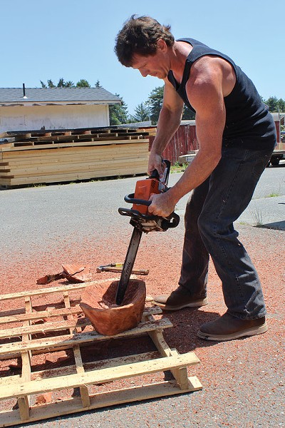 Jacob Brauning of Tall Tree Designs uses a small chainsaw to rough out a burl bowl at Furniture Fest on Sunday, June 8 at Redwood Acres in Eureka. - PHOTO BY BOB DORAN