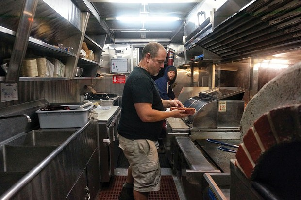 Jason Meyer, owner of Crush, and Shawn Phillips, put out one last order for the night at the brand new food truck, Retro Wagon, parked behind Redwood Curtain Brewery on Friday, July 11. - PHOTO BY BOB DORAN