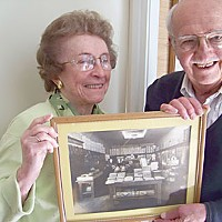Humboldt Depression Jeanne Nash and her brother Donn Johnson with a photo of the inside of their father's clothing store for men, Arthur Johnson's, in the 1930s. Photo by Heidi Walters