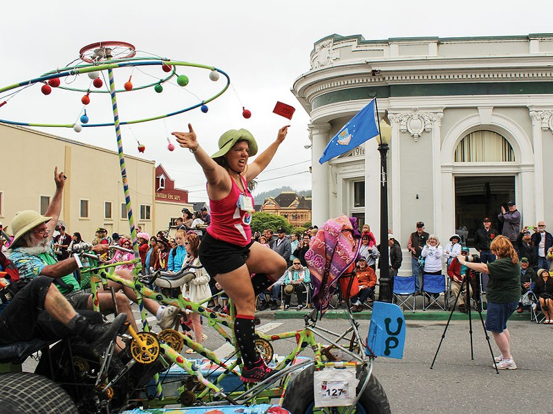 "Jerri Wagner joyously crosses the finish line of the 46th annual Kinetic Grand Championship on the rolling, spinning sculpture ""Up!"" The 42-mile Memorial Day weekend trek concluded on Ferndale's Main Street on Monday, May 27. - PHOTO BY BOB DORAN"