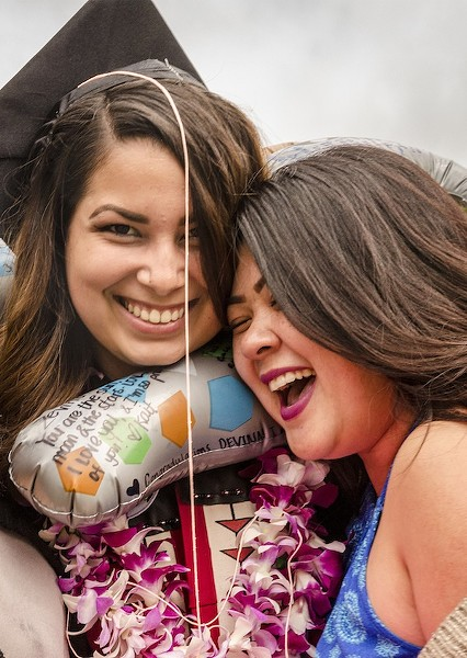 Kaitlyn Antonio, of Riverside, shared a burst of aerosal string and then a hug with her former room-mate Devina Miller, sociology major, after the ceremony.. - MARK LARSON