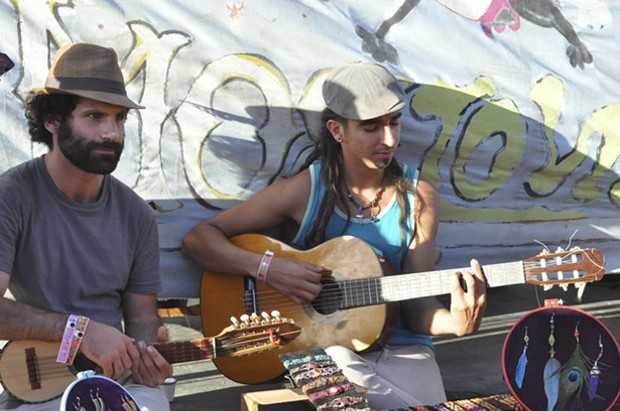 Local crafts people start an impromptu jam session while trying to stay cool at Summer Arts in Benbow. - ©TRAVIS TURNER