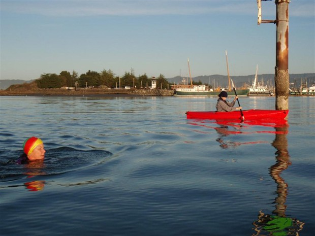 Louisa Rogers swims in the bay, spotted by a kayaker - PHOTO BY BARRY EVANS