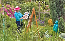 Lynne Wells painting in her garden. Photo courtesy of Redwood Art Association.