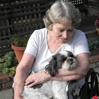 Marcia Murray cuddles Wicket, a nurse's dog, in an outdoor patio at Eureka Rehabilitation & Wellness Center.