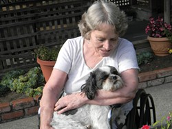 PHOTO BY CARRIE PEYTON DAHLBERG - Marcia Murray cuddles Wicket, a nurse's dog, in an outdoor patio at Eureka Rehabilitation & Wellness Center.