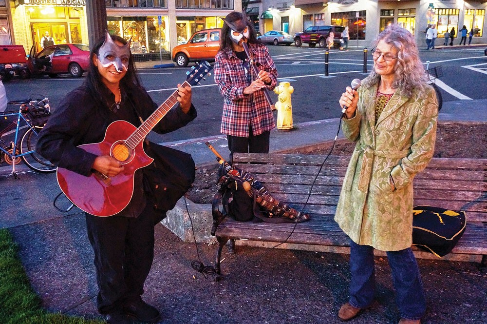 Masked guitarist Goodshield Aguilar and flautist Mignon Geli back singer Linda Faye Carson as the trio busks on the Plaza during Arts! Arcata, Friday, Aug. 8. - PHOTO BY BOB DORAN