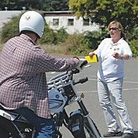 Keep Upright! Motorcycle Training instructor Deann Williams guides students in countersteering, pressing forward on the hand-grip in the direction one intends to turn. Pressing right will lean the bike to the right. Photo by Mark McKenna