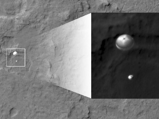 My favorite image from Curiosity's landing, taken from over 200 miles away by NASA's Mars Reconnaissance Orbiter, shows Curiosity a minute before landing, dangling beneath its 51-foot diameter parachute about two miles above Gale Crater. - NASA/JPL-CALTECH/U. OF ARIZONA
