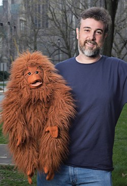 """Neuroscientist (and ventriloquist) Michael Graziano with Kevin, who helps him make the point that it's hard not to attribute some degree of consciousness to a """"talking"""" stuffed orangutang. Photo by Robert Adam Mayer"""