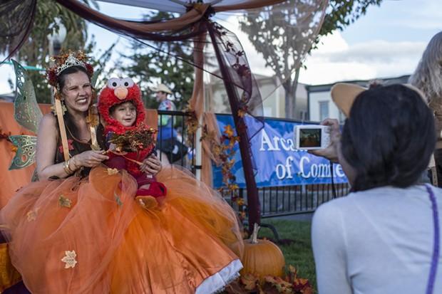Shoshanna the fairy poses with Fama (Elmo), while mother Oyaseye snaps a photo. - ALEXANDER WOODARD