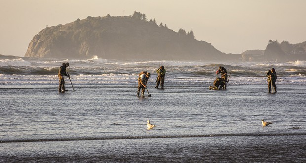 Lots of clam diggers were out on the north end of Clam Beach at sunset along with a very low tide  looking for the elusive but very tasty razor clam on Tuesday, Jan. 20. Using a long telephoto lens compressed the distance between Trinidad Head to the north and those looking for clams. - MARK LARSON