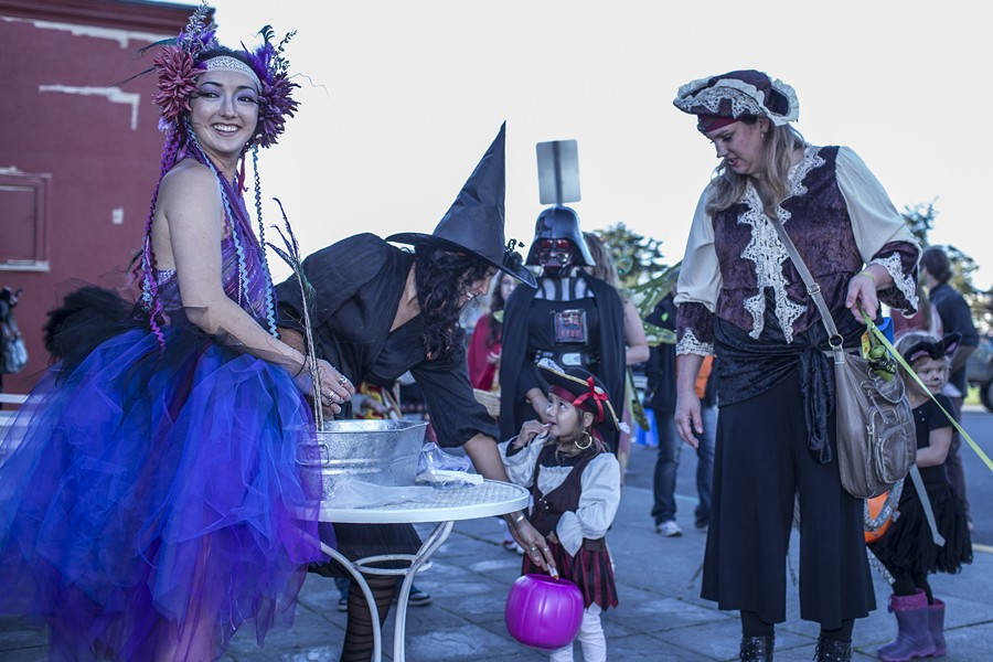 Grace Ivers, left, and Morgan Mireles of Cafe Brio, hand out candy to 2-year-old pirate Lela Aspuria and her mom Jennifer. - ALEXANDER WOODARD
