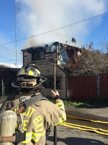 Humboldt Bay Fire crews work to vent the roof. - MARK MCKENNA