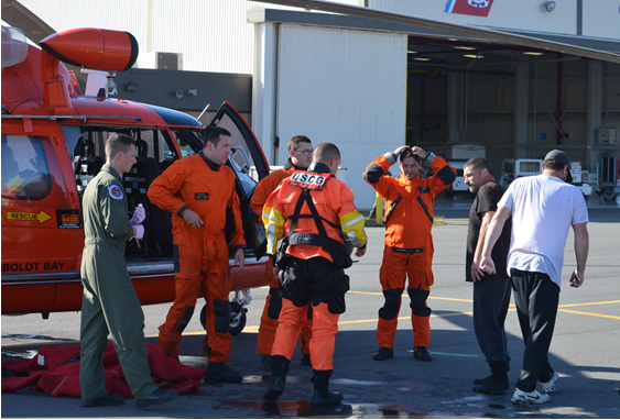 "Safely on the ground, survivors and the Coast Guard crew of a MH-65 Dolphin helicopter discuss the rescue of the crew of the vessel ""Kellen A"" off of Punta Gorda. - US COAST GUARD"