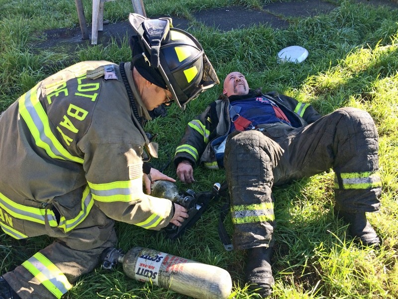 A firefighter assists another who was complaining of overheating at the scene of Saturday's fire. - MARK MCKENNA