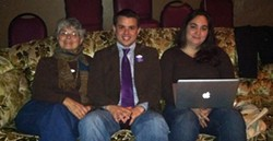PHOTO BY SCOTTIE LEE MEYERS - Newly elected city council member Shane Brinton cozies up next to his Mom, Susan Brinton (left), and Kaitlin Sopoci-Belknap to watch election results trickle in.