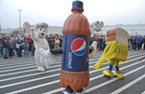 No one's happier about the new wal-mart than bimbo bear, this walking pepsi bottle and ... is that bread wearing a skirt?