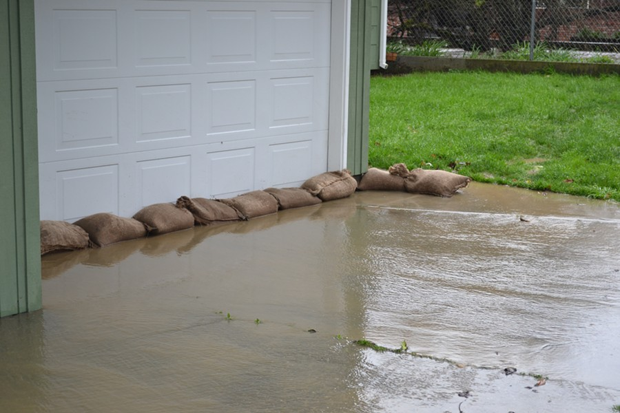Residents in low-lying areas use sandbags to keep localized flooding from seeping into their homes. - MELISSA SANDERSON
