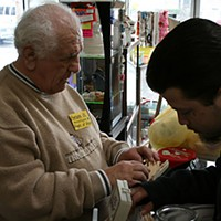 "Thrift Store Angels Senior volunteer ""Awesome"" Al Parodi assists Mike Deleon with a purchase. While Deleon has gone on to another job, he still had store credit earned during his time working at the thrift store. Photo by Bob Doran"