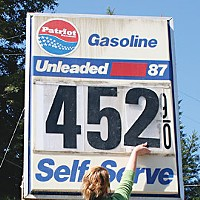 Crude Figures Sign of the times: Shelly O'Brien changes gas prices at Indianola Market. Photo by Yulia Weeks.