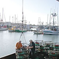 People of the Crab Skipper Jim Blum and Paul Williamson offloading crab pots from the 'Tempest.' Photo by Heidi Walters.