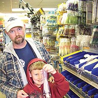 Two If By Sea Sport fisherman Eric Justesen and his son Leland shop for lures at the Englund Marine big sale. Photo by Heidi Walters