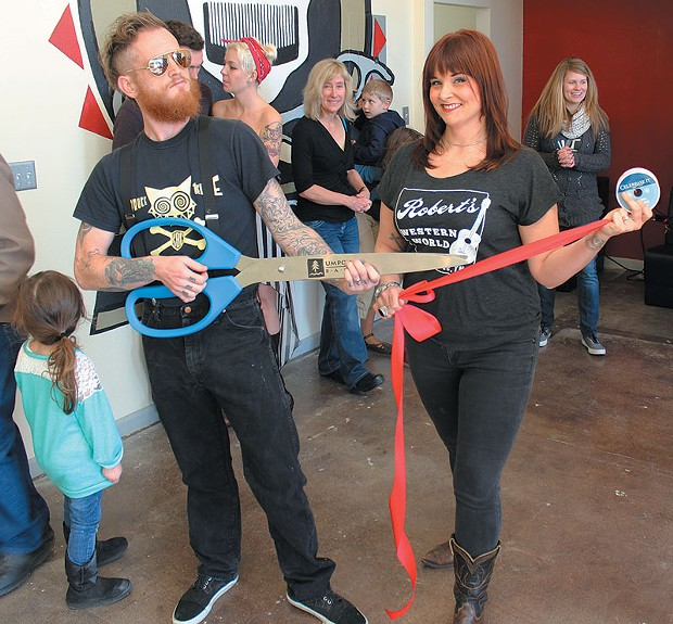 The mandolinist for The Hill, Burly Dent, and his hair cutting partner Nikki Mock prepare to cut the ribbon at their new hair salon in Arcata.