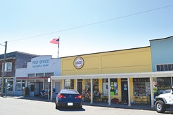 PHOTO BY HEIDI WALTERS - The throbbing heart of Main Street, Loleta, these days is that yellow building. It harbors a popular bakery and an 81-year-old meat market/town hub. To either side of it lie the post office and a busy little grocery store.
