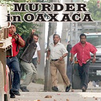 This photo, taken just as Brad Will was killed, shows clearly identifiable Oaxaca police officers firing at the crowd. See end of story for more details.