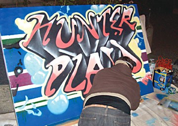 Tommy Warsaw spray-paints a sign for an Arts! Arcata opening. Photo by Jeff Hunter