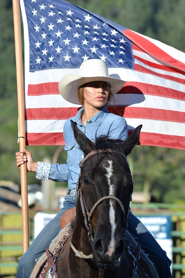A Native woman carries the flag during the Hoopa Rodeo. - PHOTO BY EVE FREEDMAN