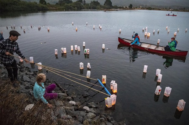 Volunteer Tony Wallin, of Arcata, helped move the lighted lanterns away from the shore into the gentle breeze blowing across Klopp Lake. - PHOTO BY MARK LARSON