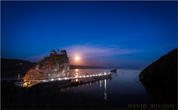 The full moon rises over Little Head, Trinidad Pier, and Trinidad Harbor. Trinidad Head is the silhouetted land mass on the right. - DAVID WILSON