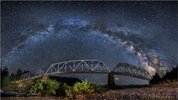 The Milky Way arcs from horizon to horizon above the South Fork Bridge in this panorama on the Main Fork Eel River, Humboldt County, California. July, 2018. - DAVID WILSON