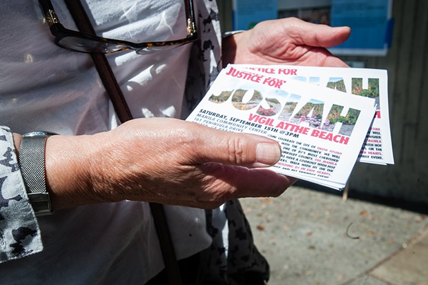 Meg Stofsky holds handbills for a Justice for Josiah vigil happening this weekend at the Manila Community Center. - PHOTO BY MARK MCKENNA