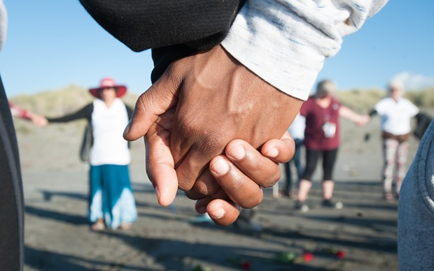 Vigil attendees joined hands in a circle to remember David Josiah Lawson. - MARK MCKENNA