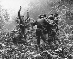 Eric Hollenbeck is just out of frame in this iconic photograph. His long-held belief that the man lifting his arms in the air is the Sergeant he shadowed throughout the war was finally confirmed in 2014. / Courtesy of Art Greenspon.