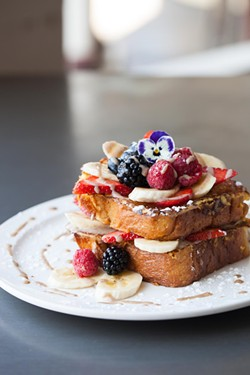 Banana-stuffed French toast with fresh berries at T's. - AMY KUMLER