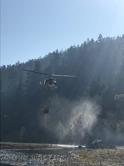 A Cal Fire helicopter pulls water from the Eel River. - KORY BEACH