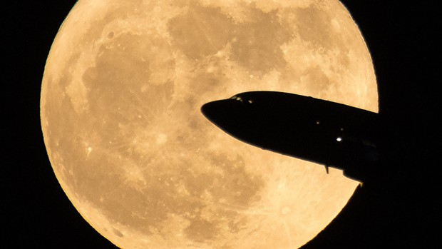 An aircraft taking off is seen passing in front of full moon in December of 2017. - NASA/BILL INGALLS