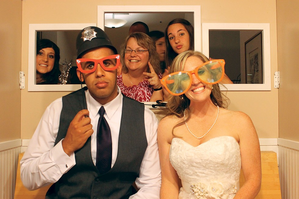 Lyndon and Brittany Powell ham it up in a Sunny Nights photo booth - at their wedding. Guests Ashley Pearce, Carolyn Barnhart and Jenna Barnhart photobomb from behind. - SUNNY NIGHTS PHOTO BOOTH