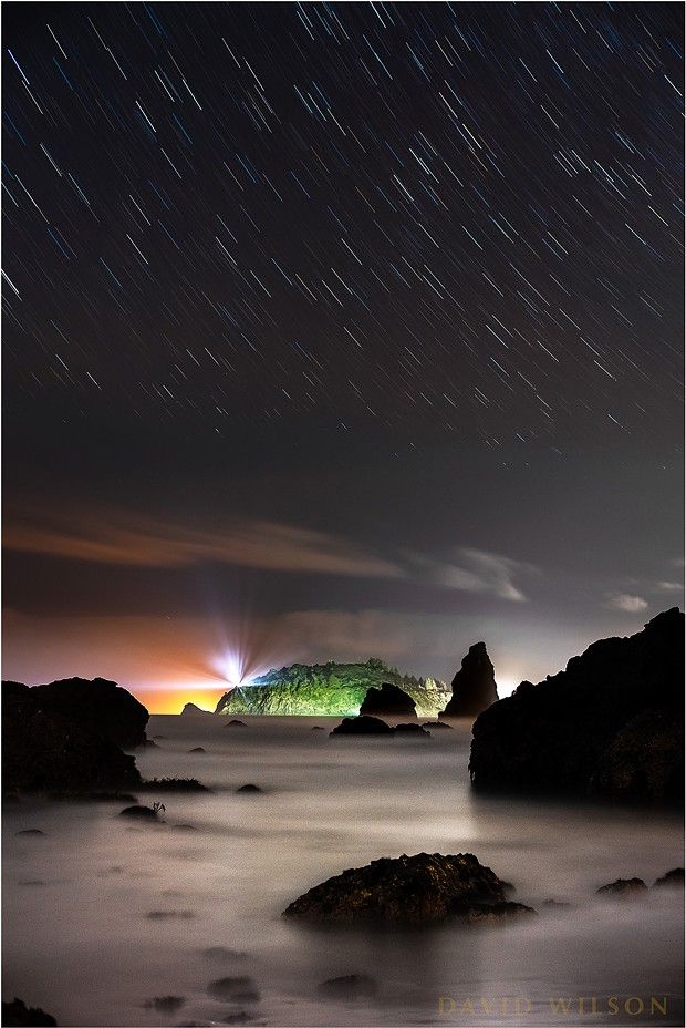 Looking north toward Trinidad and Trinidad Head from Houda Point Beach, Humboldt County, California. This is actually a little west of north, as you can see from the arc of the star trails that the North Star, Polaris, would be above and to the right of this view. The star trails closer to the cloud layer appear to break up in places due to being partially obscured at times by the moving clouds. Like a skylight cover the cloud layer slid until the stars were replaced by grey. Same thing happened to my hair. - DAVID WILSON