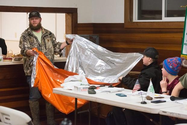 Justin Lehnert holds up a survival blanket during the Miranda 4-H meeting. - MARK MCKENNA