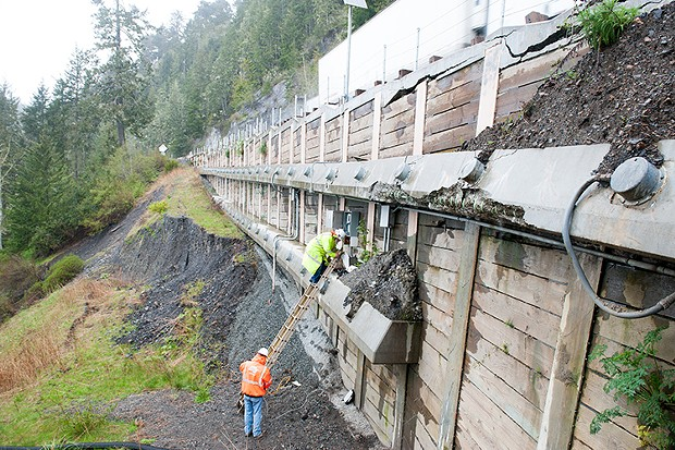 Workers gather data from load sensors on a retaining wall at one of the fail points. - PHOTO BY MARK MCKENNA