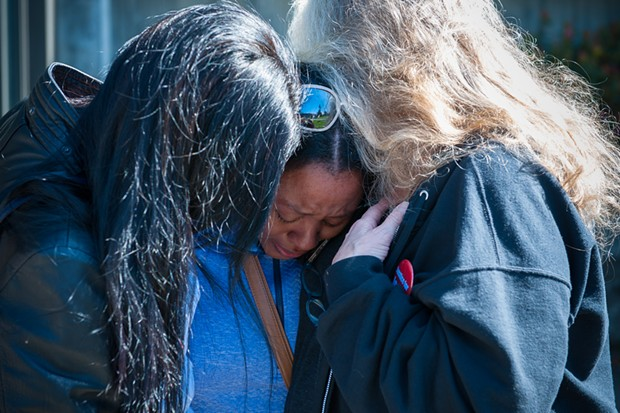 Charmaine Lawson is hugged by supporters shortly before addressing students, faculty and the community on the HSU Quad on Friday, the 23-month anniversary of the killing of her son, David Josiah Lawson. - MARK MCKENNA