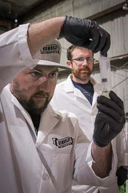 Skyler Palmer, head of cultivation at HendRx Farms, looks on as Humboldt Seed Co. founder Nat Pennington prepares a cannabis sample for testing. - PHOTO BY THADEUS GREENSON