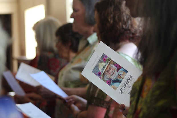 """A member of the Threshold Choir opens up Thompson's memorial program where lyrics to the song """"Walking Each Other Home,"""" is printed. The group and attendees ended the memorial service arm in arm while singing this song together. - PHOTO BY NATALYA ESTRADA"""